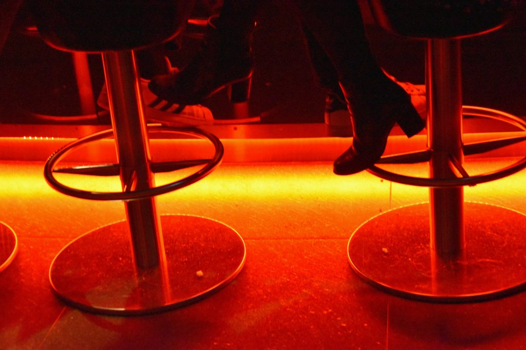 Bar stools at a cocktail lounge with orange lighting.